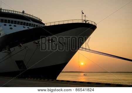 Cruise ship docked at port at sunset