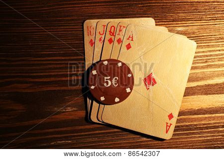 Playing cards with chips on wooden background