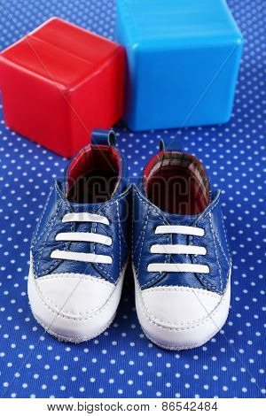 Baby shoes on blue cloth background