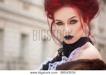 sexy woman with gothic makeup and red hair and castle
