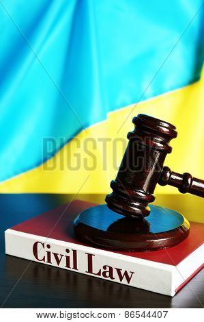 Wooden gavel and flag of Ukraine as background
