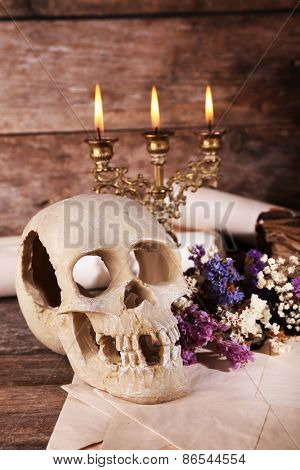 Still life with human skull and candlelight on wooden table, closeup