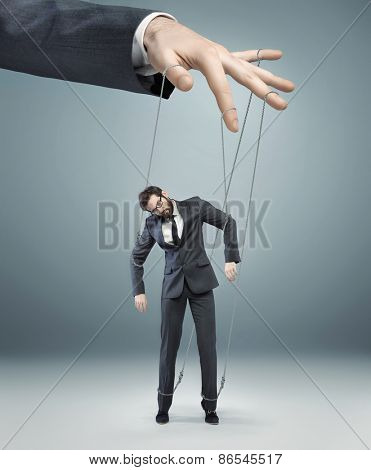 Businessman's hand controlling a worker