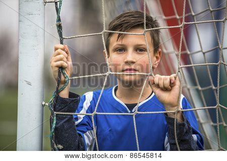 Portrait of a little boy in goalkeeper uniform behind mesh football goal on the stadium.