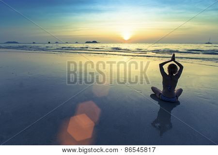 Silhouette of yoga woman meditating on the ocean beach.