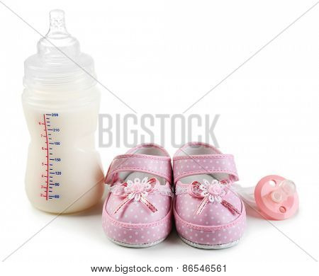 Baby shoes with nipple and bottle of milk isolated on white