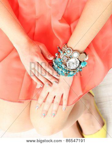 Stylish bracelets and clock on female hand close-up
