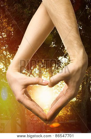 Heart shaped by male and female hands on nature background