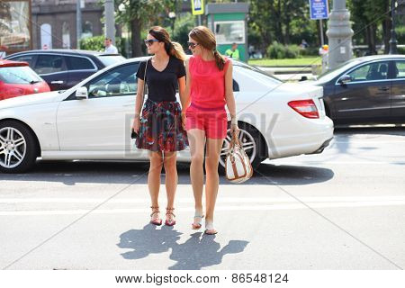 Two young girls girlfriends cross the road in the wrong place