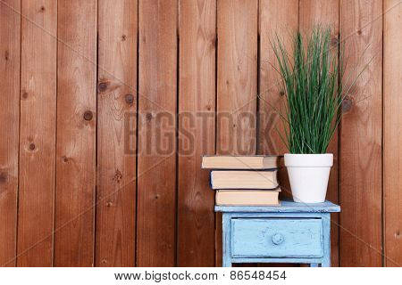Interior design with plant and stack of books on tabletop on wooden planks background
