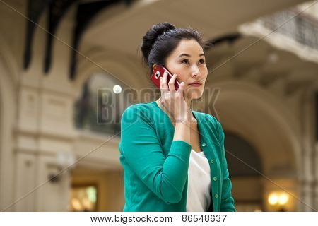 Beautiful asian talking on the mobile phone, indoor