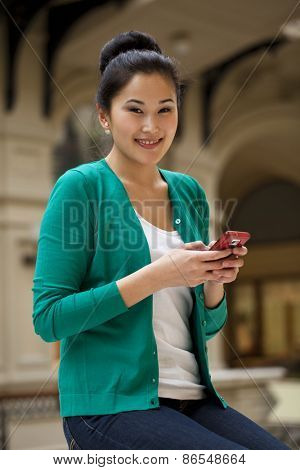 Young beautiful asian holding a cell phone
