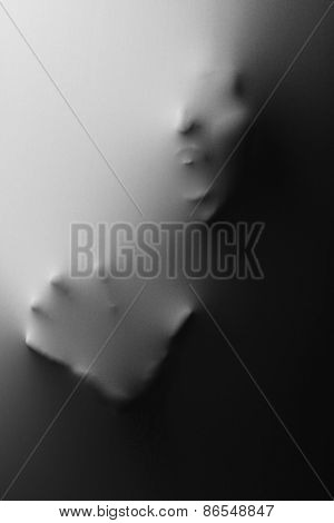 Screaming human face with hand pressing through fabric as horror background