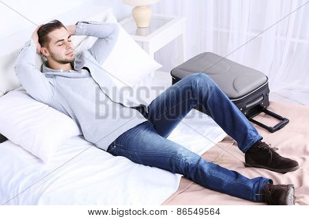 Tired man resting on bed in room