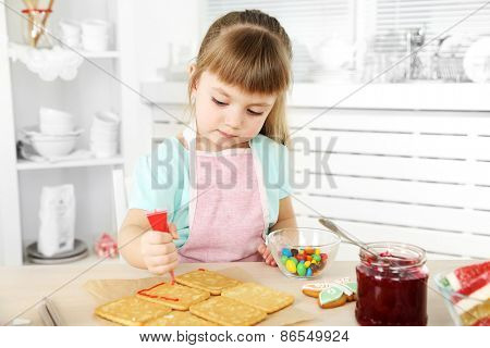 Little girl decorating prepared cookies in kitchen at home