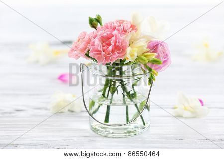 Beautiful spring flowers in glass bottle on wooden background