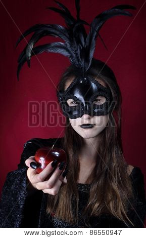 A girl in period gothic attire offers an apple