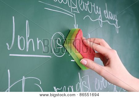 Teacher hand wiping off sentences from blackboard background