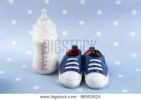 Baby shoes with bottle of milk on blue background