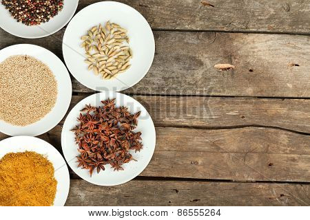 Different spices on plates, on old wooden table