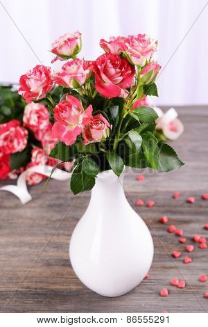 Beautiful roses in vase on table on light background