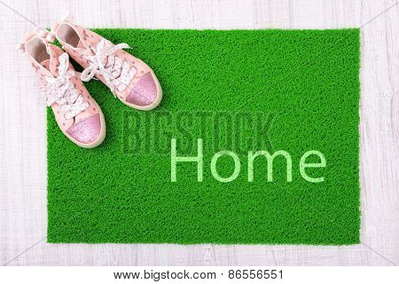 Sneakers and green carpet on floor