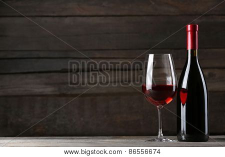 Wine bottle with glass on wooden background