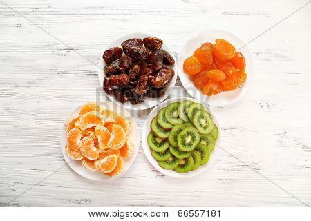 Different products on saucers on wooden background