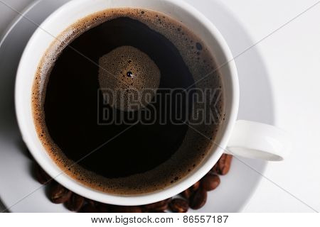 Cup of coffee with grains, top view