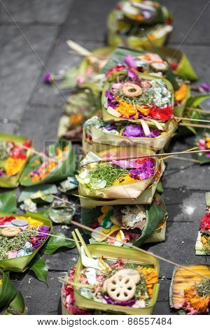 Traditional Balinese offerings to gods in Bali with flowers and aromatic sticks