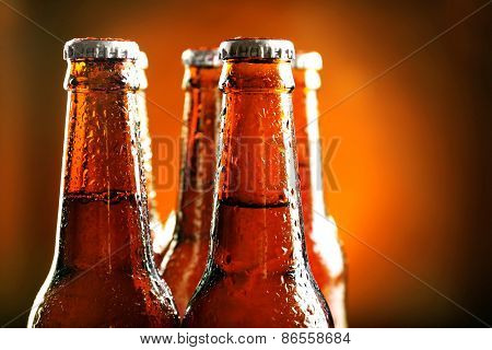 Glass bottle of beer on dark background