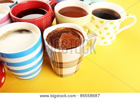 Many cups of coffee on yellow background