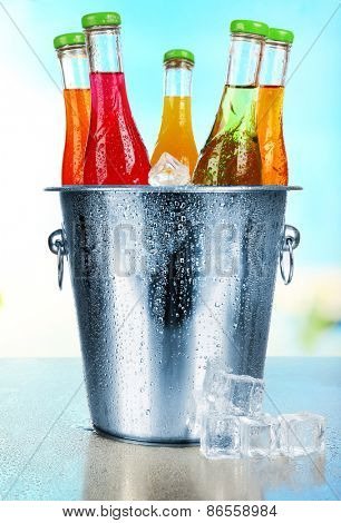 Bottles of tasty drink in metal bucket with ice on bright background