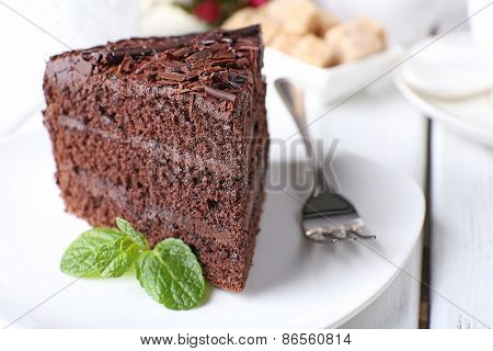 Piece of delicious chocolate cake with mint in plate with fork on color wooden table background