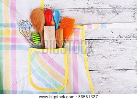 Set of kitchen utensils in pocket of apron on wooden background