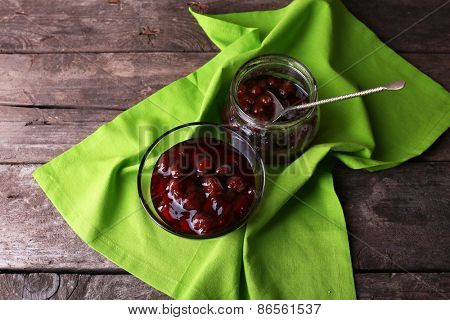Tasty jam in bowl and jar with napkin on wooden background