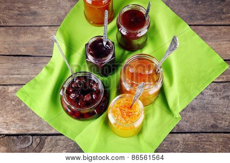 Jars of tasty jam with napkin on wooden background