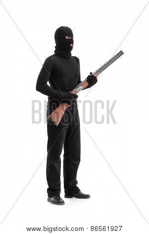 Full length portrait of a dangerous criminal holding a shotgun rifle isolated on white background, studio shot