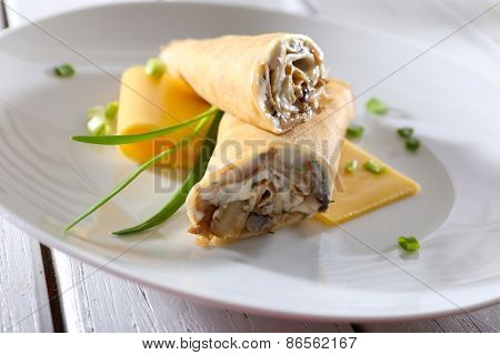 Pancakes with cream and mushrooms on wooden table, closeup