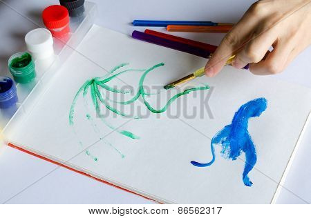 Left Hand Draws Brush With Green Paint On Paper In Album With Several Colorful Brushes Near