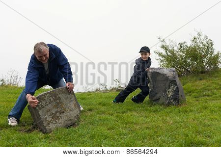 Senior And Child Moving Big Boulder