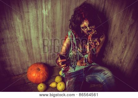 Terrible bloody zombie girl sitting by the old wall and pumpkins. Horror. Halloween.