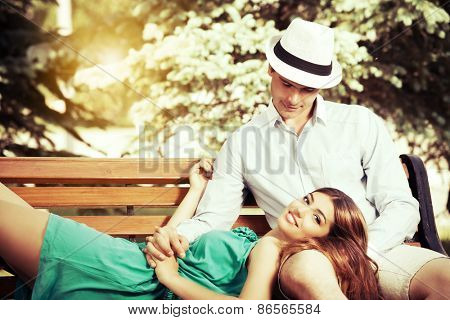 Romantic young people tenderly  talking on a park bench. Love concept.