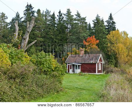 A red little cabin this side a forest.