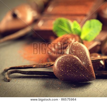 Chocolates background. Chocolate. Assortment of fine chocolates in dark and milk chocolate with vanilla and mint. Praline Chocolate sweets. Heart shaped