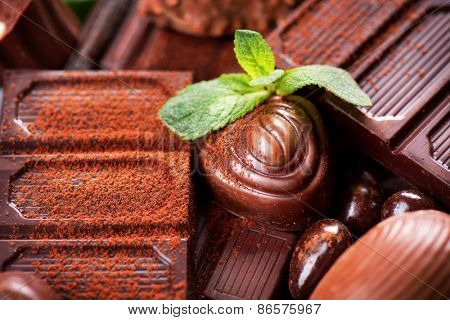 Chocolate background. Chocolate. Assortment of fine chocolates in dark and milk chocolate with mint. Praline Chocolate sweets