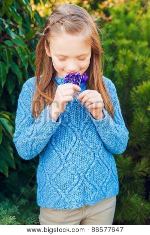Outdoor portrait of a cute little girl of 7 years old, wearing blue pullover