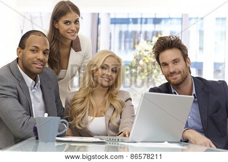 Portrait of successful businessteam sitting at table, working, smiling happy.