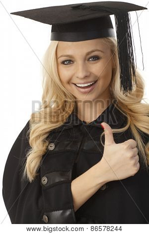 Closeup photo of happy blonde female graduate showing thumb-up sign.