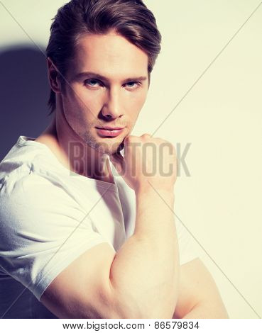Portrait of handsome young man with hand near face in white t-shirt poses over wall with contrast shadows.